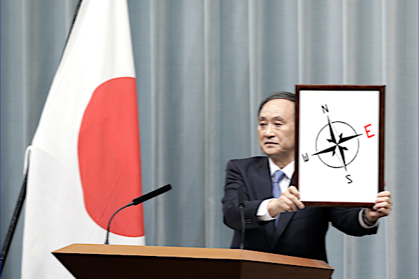 """Izanagi holding up a framed photograph of a compass with the red """"E"""" for east highlighted"""